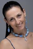 Retrato de la muchacha alegre con los pendientes y el collar Foto de archivo libre de regalías