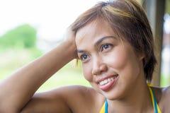 Ciérrese encima del retrato de la mujer asiática hermosa feliz joven de Indonesia que mira el soñar despierto y pensamiento pensa Imagen de archivo