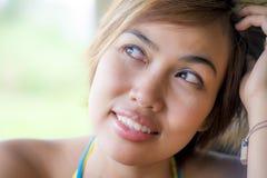 Ciérrese encima del retrato de la mujer asiática hermosa feliz joven de Indonesia que mira el soñar despierto y pensamiento pensa Imagenes de archivo
