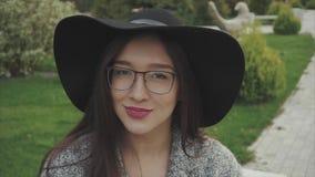 Ciérrese encima del retrato de la mujer bonita en sombrero negro y vidrios en el parque al aire libre almacen de metraje de vídeo