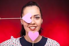 Ciérrese encima del retrato de la mujer con dos corazones rosados Fotografía de archivo