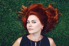Ciérrese encima del retrato de la mujer hermosa caucásica joven de la muchacha con el pelo rojo marrón que miente en hierba verde Foto de archivo
