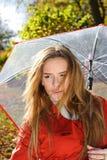 Ciérrese encima del retrato de la mujer hermosa joven en parque del otoño con el paraguas rojo Imágenes de archivo libres de regalías