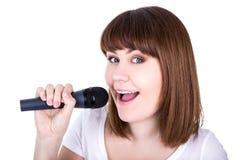 Ciérrese encima del retrato de la mujer hermosa joven que canta con micropho Foto de archivo libre de regalías