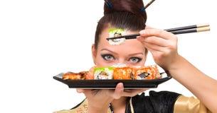 Ciérrese encima del retrato de la mujer joven con el sushi Imagenes de archivo