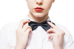 Ciérrese encima del retrato de la mujer joven en la camisa y la corbata de lazo blancas con el lápiz labial rojo fotos de archivo