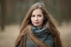 Ciérrese encima del retrato de la mujer joven hermosa con el pelo extralargo magnífico que presenta en tiempo ventoso del parque  Imagen de archivo