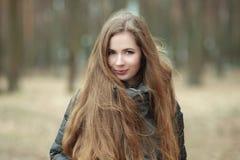 Ciérrese encima del retrato de la mujer joven hermosa con el pelo extralargo magnífico que presenta en tiempo ventoso del parque  Imagenes de archivo
