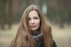 Ciérrese encima del retrato de la mujer joven hermosa con el pelo extralargo magnífico que presenta en tiempo ventoso del parque  Fotografía de archivo