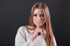 Ciérrese encima del retrato de la mujer joven hermosa en el suéter blanco y vaqueros, aislado en fondo negro Imágenes de archivo libres de regalías