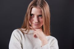 Ciérrese encima del retrato de la mujer joven hermosa en el suéter blanco y vaqueros, aislado en fondo negro Fotografía de archivo