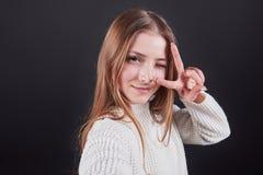 Ciérrese encima del retrato de la mujer joven hermosa en el suéter blanco y vaqueros, aislado en fondo negro Fotos de archivo