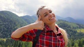 Ciérrese encima del retrato de la mujer joven hermosa que sonríe en el fondo de la naturaleza de la montaña metrajes