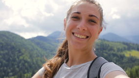 Ciérrese encima del retrato de la mujer joven hermosa que sonríe en el fondo de la naturaleza de la montaña almacen de metraje de vídeo