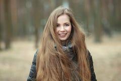 Ciérrese encima del retrato de la mujer joven hermosa sonriente con el pelo extralargo magnífico que presenta en tiempo ventoso d Foto de archivo libre de regalías