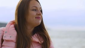 Ciérrese encima del retrato de la mujer joven que sonríe con el pelo marrón que sopla en el viento que mira el arround metrajes