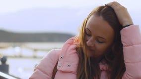 Ciérrese encima del retrato de la mujer joven que sonríe con el pelo marrón que sopla en el viento que mira el arround almacen de video