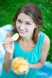 Ciérrese encima del retrato de la mujer linda que come las patatas fritas Imágenes de archivo libres de regalías