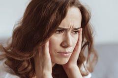 Ciérrese encima del retrato de la mujer que lucha con dolor de cabeza Imagen de archivo
