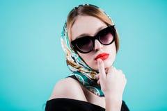 Ciérrese encima del retrato de la mujer rubia hermosa en gafas de sol y bufanda en fondo azul Muchacha con los labios rojos brill Imagen de archivo