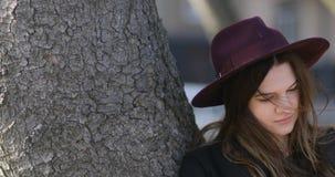 Ciérrese encima del retrato de la mujer sonriente bonita con el sombrero usando la tableta en el parque 4k, steadicam almacen de video