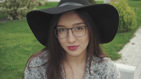 Ciérrese encima del retrato de la mujer sonriente bonita en sombrero negro y vidrios en el parque metrajes