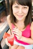 Ciérrese encima del retrato de la mujer sonriente joven con el ju de la sandía Imagen de archivo