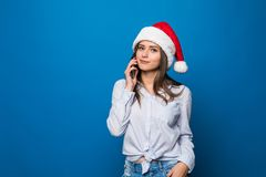 Ciérrese encima del retrato de un adolescente bonito alegre en el sombrero de santa que habla en el teléfono móvil sobre fondo az Foto de archivo