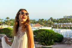 Ciérrese encima del retrato de un adolescente en el vestido y las gafas de sol blancos en un parque durante un día soleado, miran Foto de archivo