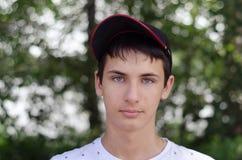 Ciérrese encima del retrato de un adolescente lindo en una gorra de béisbol Foto de archivo