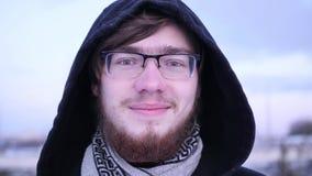 Ciérrese encima del retrato de un hombre joven atractivo que sonríe en la cámara cekntelleo Fondo borroso del invierno Cámara len metrajes