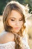 Ciérrese encima del retrato de un modelo hermoso de la señora joven en campo en la puesta del sol Fotografía de archivo libre de regalías