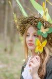 Ciérrese encima del retrato de una muchacha en un anillo de flores Imagen de archivo