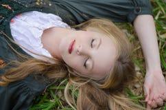 Ciérrese encima del retrato de una muchacha que duerme en la hierba Fotografía de archivo libre de regalías