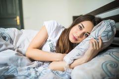 Ciérrese encima del retrato de una mujer bonita joven tranquila que duerme y que abraza la almohada en cama Imagenes de archivo