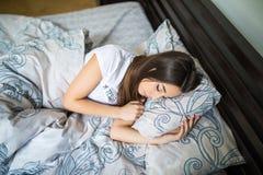 Ciérrese encima del retrato de una mujer bonita joven tranquila que duerme y que abraza la almohada en cama Imagen de archivo libre de regalías