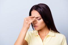 Ciérrese encima del retrato de una mujer hispánica joven que tiene afte del dolor de cabeza foto de archivo