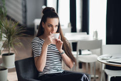 Ciérrese encima del retrato de una mujer que se sienta cerca de ventana y que prueba un café de una taza en un restaurante Imágenes de archivo libres de regalías