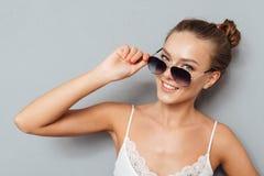 Ciérrese encima del retrato de una mujer sonriente que sostiene las gafas de sol Foto de archivo libre de regalías