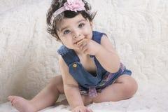Ciérrese encima del retrato de una niña feliz que come la galleta y mire fotografía de archivo