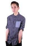 Ciérrese encima del retrato del adolescente joven en la camisa gris, manos en bolsillos Aislado en el fondo blanco Imagen de archivo
