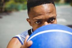 Ciérrese encima del retrato del adolescente masculino que lleva a cabo baloncesto Foto de archivo