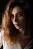 Ciérrese encima del retrato del estudio de la mujer joven en la blusa blanca en fondo negro imágenes de archivo libres de regalías