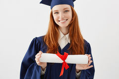 Ciérrese encima del retrato del graduado astuto feliz de la muchacha en casquillo que sonríe sosteniendo el diploma Abogado joven Foto de archivo libre de regalías
