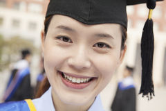 Ciérrese encima del retrato del graduado joven sonriente de la hembra que lleva un birrete Fotografía de archivo