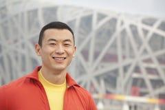 Ciérrese encima del retrato del hombre atlético joven sonriente en parque, mirando la cámara, con el edificio moderno en el fondo  Fotos de archivo libres de regalías
