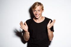 Ciérrese encima del retrato del hombre joven hermoso rubio sonriente alegre que lleva las manos que aplauden de la camiseta negra Fotografía de archivo