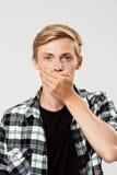 Ciérrese encima del retrato del hombre joven rubio confiado hermoso que lleva la boca casual de la cubierta de la camisa de tela  Foto de archivo libre de regalías