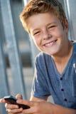 Ciérrese encima del retrato del muchacho con el teléfono al aire libre. Foto de archivo