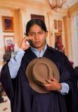Ciérrese encima del retrato del sombrero que lleva y del poncho del hombre indígena joven usando el teléfono celular fotos de archivo